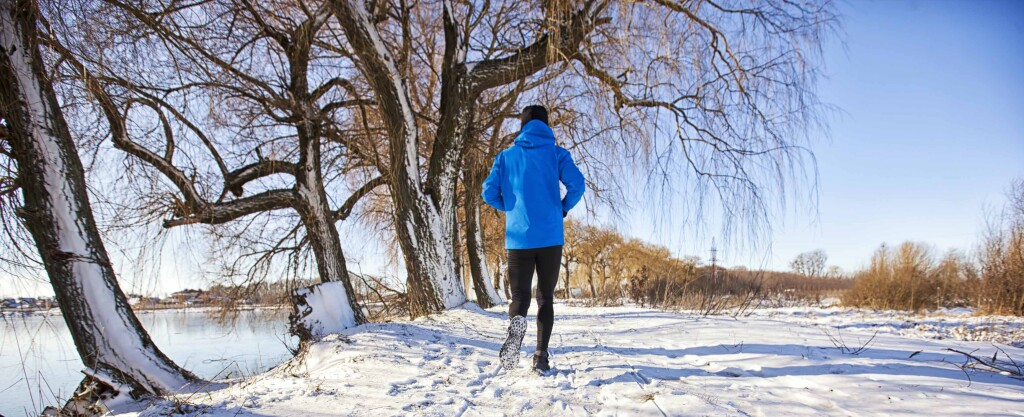 The man in sportswear is jogging through the winter country road